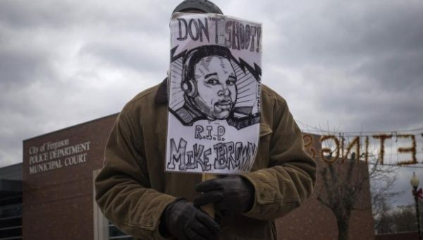 A protester holds an image of Michael Brown in Ferguson, after the unarmed, black teen was shot by a white police officer last summer.