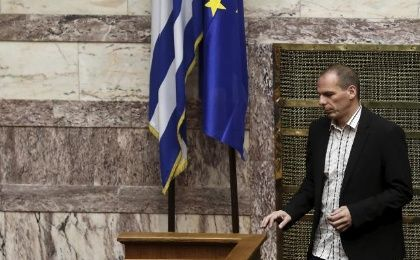 Greek Finance Minister Yanis Varoufakis walks next to a European Union and a Greek national flag during a parliamentary session in Athens April 2, 2015.