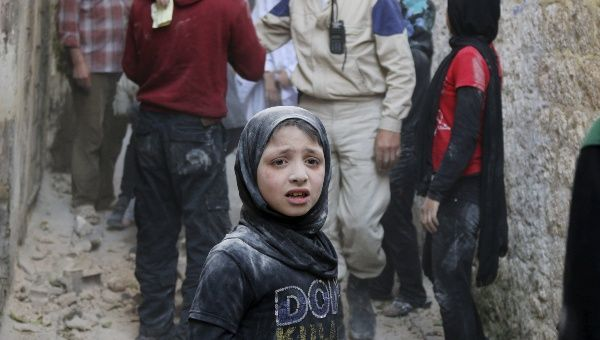 A girl reacts at a site hit by what activists said was a ground-to-ground missile fired by forces of Syria