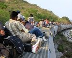 People hoping to reach the U.S. ride atop the wagon of a freight train, known as La Bestia (The Beast) in Ixtepec.