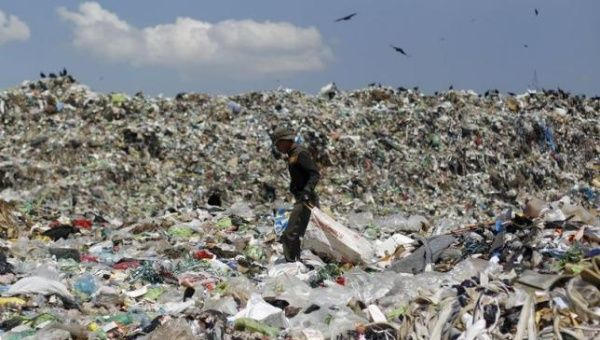 A man looks for usable items in a dumpsite on the outskirts of Tegucigalpa, April 17, 2015.