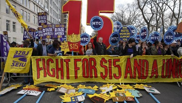 Demonstrators hold signs during demonstrations asking for higher wages in the Manhattan borough of New York April 15, 2015.