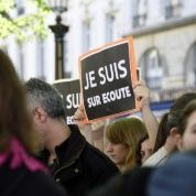 "A protester holds a banner reading ""I am wiretapped"" in the ""Je suis Charlie"" style."