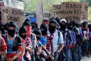 Members of the EZLN hold banners saying Members of the EZLN hold banners saying