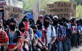 Members of the EZLN hold banners saying