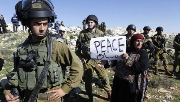 A protester holds a placard as she stands next to Israeli soldiers during a protest against Israeli settlements in Beit Fajjar town south of the West Bank city of Bethlehem December 27, 2014.