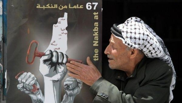 A Palestinian man touches a poster displayed on a door announcing the Nakba commemorations on May 14, 2015, at the al-Fawar refugee camp in the West Bank town of Hebron.