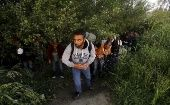 A group of Syrian immigrants hide as they walk towards Greece's border with Macedonia in Kilkis prefecture, May 14, 2015.