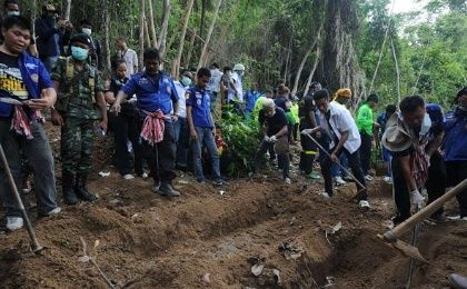 Rescue workers and forensic officials dig out skeletons from shallow graves covered by bamboo at the site of a mass grave at an abandoned jungle camp in the Sadao district of Thailand's southern Songkhla province bordering Malaysia.