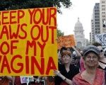 Women's rights activists carry signs during an abortion rights march in Austin, Texas, July 8, 2013.