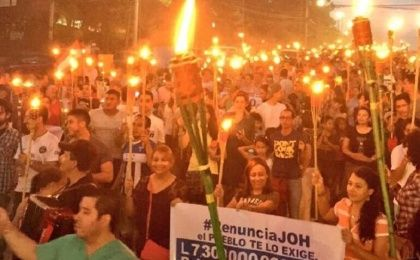 "Protesters carry torches and signs that read ""JOH resign"" to demand the president"