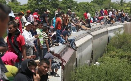 Migrants ride on top of a freight train, called