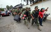 A member of the teacher's union CNTE (R) yells while walking alongside soldiers after they were forced to leave the premises of Mexico's National Electoral Institute (INE) in Oaxaca June 2, 2015