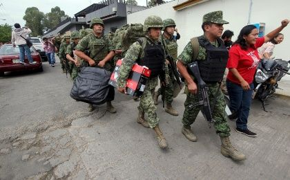 A member of the CNTE yells while walking alongside soldiers after they were forced to leave the INE premises in Oaxaca, June 2, 2015