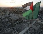 The flags of Palestine and Hamas fly over devestation in Gaza left by last-year's air strikes.