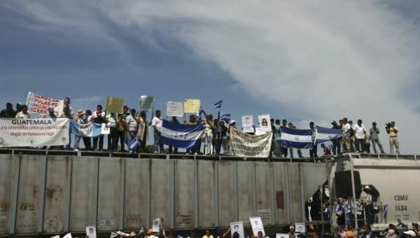 "Migrants holding Guatemalan and Honduran flags ride on the freight train known as ""The Beast"" to travel across Mexico on route to the United States."