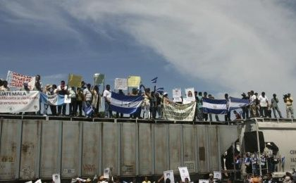 Migrants holding Guatemalan and Honduran flags ride on the freight train known as