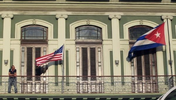 A man stands near the national flags of the U.S. and Cuba (R) on the balcony of a hotel being used by the first U.S. congressional delegation to Cuba since the change of policy announced by U.S. president Barack Obama