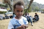 A child waits with migrants at the border between Italy and France in the city of Ventimiglia, Italy.