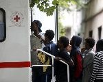 Migrants await a visit by Red Cross in front of the migration centre next to the Tiburtina station in Rome, June 12, 2015.