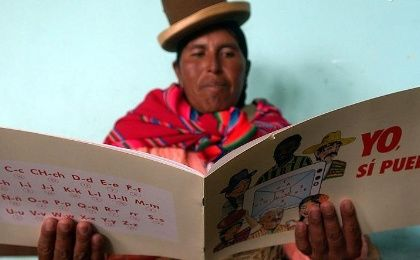 A Bolivian woman learns to read from a book called