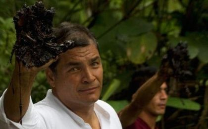 Ecuadorean President Rafael Correa holds up his oil-covered hand as proof of contamination in the amazon.