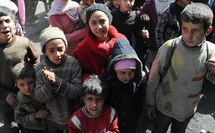 Children from Syria's besieged Yarmuk Palestinian refugee camp, south of Damascus, standing during a relief operation in February, 2014.