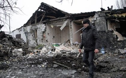 A man walks near a damaged residential building in Donetsk, eastern Ukraine January 19, 2015.