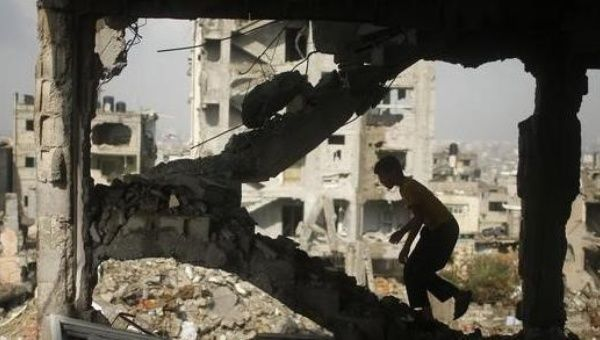 A Palestinian boy walks up the stairs inside the ruins of their house, that witnesses said was destroyed during a seven-week Israeli offensive, in the east of Gaza City October 19, 2014.