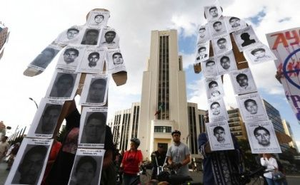 Mexico protesters hold two large effigies covered with photos of missing students that read