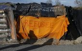 Shadows from migrants are cast on a makeshift shelter with the written word ''Refugee'' in Calais, France, April 30, 2015.