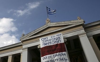 A Greek national flag flutters as a banner announcing a protest of the Greek Communist Party hangs on the facade of the University of Athens, Greece June 25, 2015.