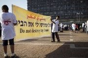Israeli Arab boys hold a banner during a protest against housing shortage and house demolitions in Arab communities, in Tel Aviv's Rabin Square, Israel April 28, 2015.