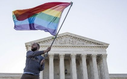 Vin Testa of Washington, DC, waves a gay rights flag in front of the Supreme Court before a hearing about gay marriage in Washington in an April 28, 2015 file photo.
