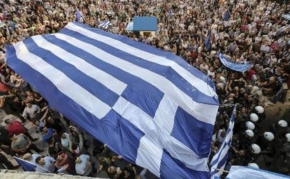 Protesters carry a gigantic Greek flag during a rally in front of the parliament building calling on the government to clinch a deal with its international creditors.