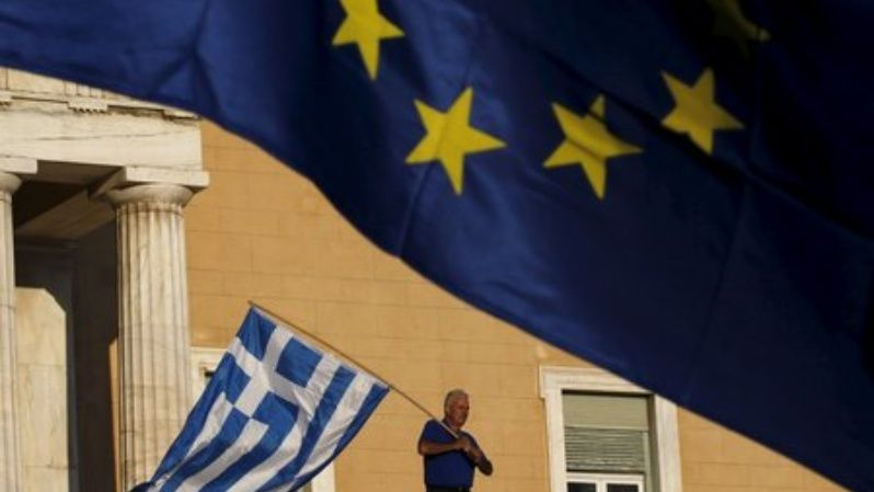 A protester waves a Greek flag at the entrance of the parliament building during a rally calling on the government to clinch a deal with its international creditors and secure Greece