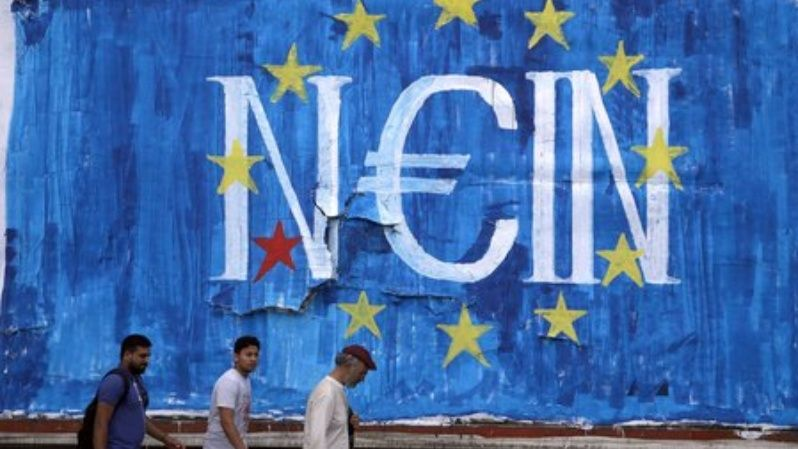 Men walk by fresh anti-EU graffiti in Athens, Greece June 28, 2015.