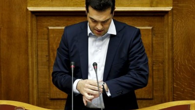 Greek Prime Minister Alexis Tsipras looks at his watch as he delivers a speech during a parliamentary session in Athens, Greece in this June 28, 2015 file photo.