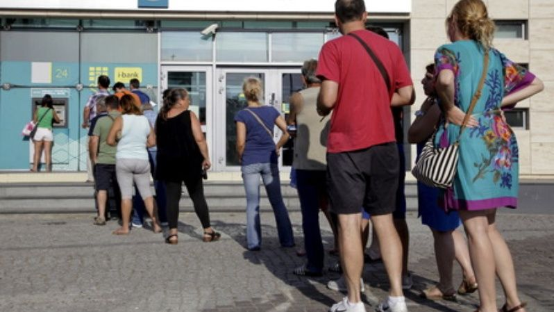 People line up to withdraw cash from an automated teller machine (ATM) outside a National Bank branch in Iraklio on the island of Crete, Greece June 28, 2015.