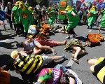 Protesters in costume act out bees and wildlife being killed by Monsanto pesticide, during a protest march prior to the G7 summit in Munich June 3, 2015.