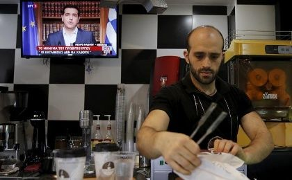 A waiter prepares coffee as the image of Greek Prime Minister Alexis Tsipras is seen on television during a live television address in Athens, Greece, July 1, 2015.