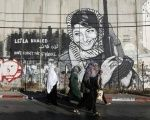 Palestinian women walk past graffiti on Israel's illegal barrier as they walk towards an Israeli checkpoint in the West Bank town of Bethlehem, during the holy month of Ramadan July 26, 2013.