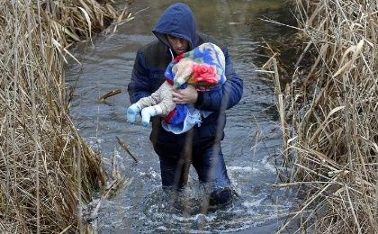 A Kosovar man carries his baby as he crosses the Hungarian-Serbian border without documents, near the village of Asotthalom, on February 6, 2015.