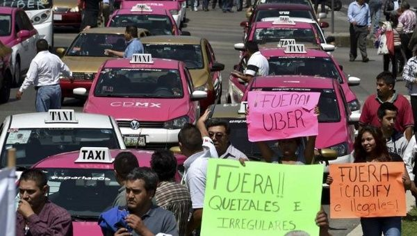 "Taxi drivers in Mexico City protest Uber over alleged unfair competition with signs that say ""Out with Uber!"" on May 25, 2015."