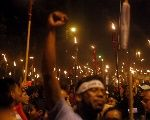 Demonstrators hold torches during a march to demand the resignation of Honduras' President Juan Orlando Hernandez in Tegucigalpa, July 10, 2015