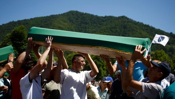 People carry coffins to graves at the Memorial Center Potocari, near Srebrenica.