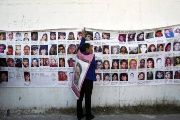 A woman holds onto a banner with the photographs of missing women in Ciudad Juarez