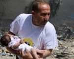 A man holds a baby that survived what activists said was a site hit by a barrel bomb dropped by forces loyal to Syrian President Bashar al-Assad at the old city of Aleppo June 3, 2015.