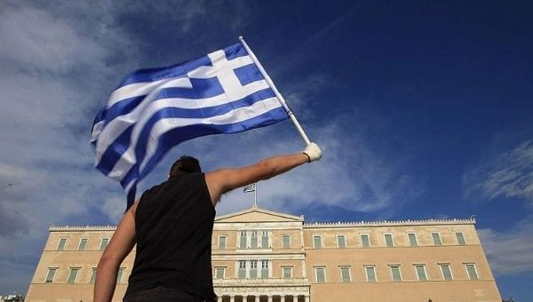 A protester raises Greek flag in front of the parliament during a rally.