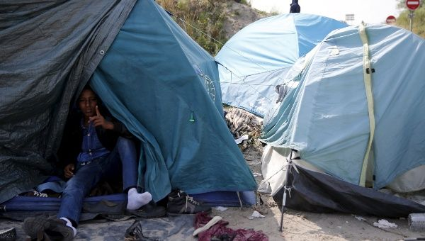 "An Ertirean migrant sits in his makeshift shelter in ""The New Jungle"" near Calais, France, August 1, 2015."